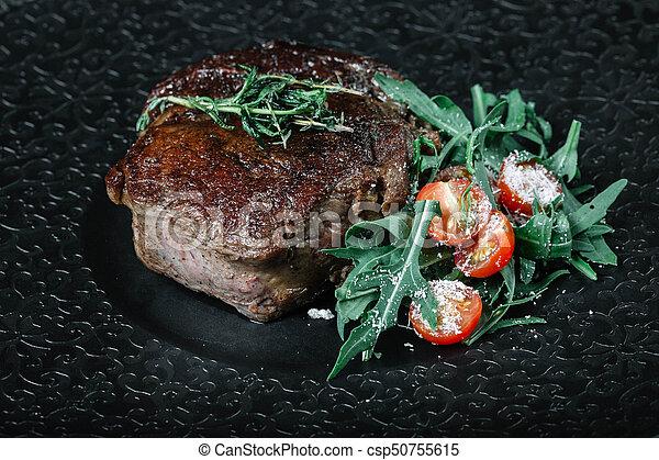 Grilled beef steak with salad on dark background - csp50755615