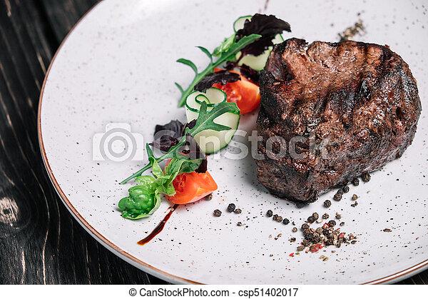 Grilled beef steak with salad on dark wooden background - csp51402017