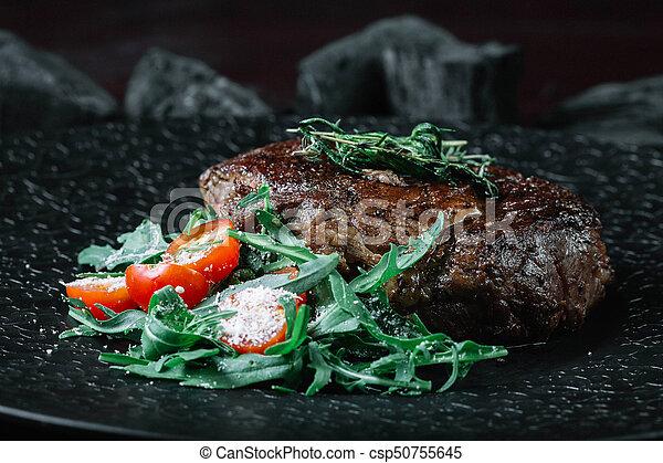 Grilled beef steak with salad on dark background - csp50755645