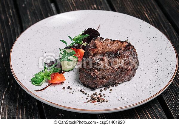 Grilled beef steak with salad on dark wooden background - csp51401920