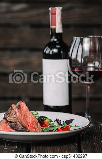 Grilled beefsteak with bottle and glass of red wine on dark wooden background - csp51402297