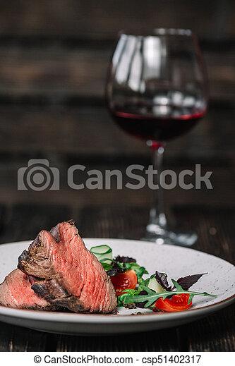 Grilled beefsteak with glass of red wine on dark wooden background - csp51402317