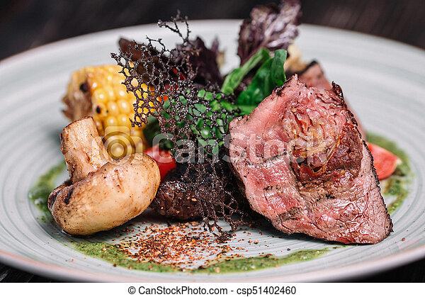 Grilled beefsteak with vegetable on dark wooden background - csp51402460