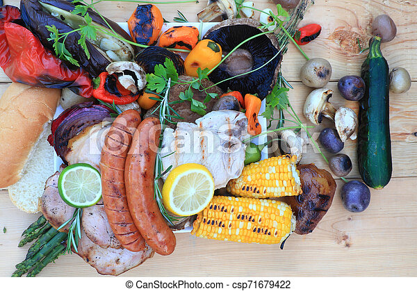 Grilled food on Camp Fire Grill over wooden table. - csp71679422