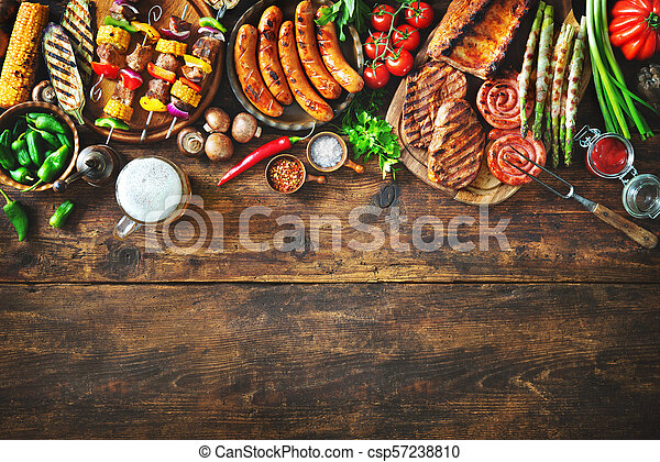 Grilled meat and vegetables on rustic wooden table - csp57238810