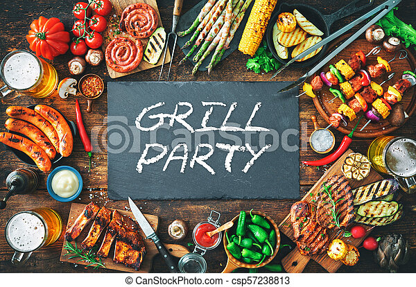 Grilled meat and vegetables on rustic wooden table - csp57238813