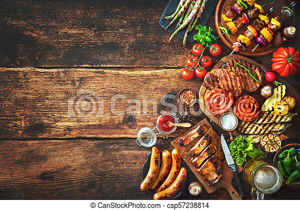 Grilled meat and vegetables on rustic wooden table - csp57238814