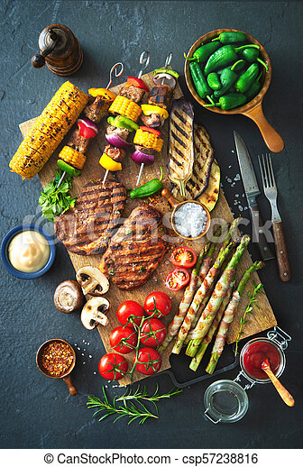 Grilled meat and vegetables on rustic stone plate - csp57238816