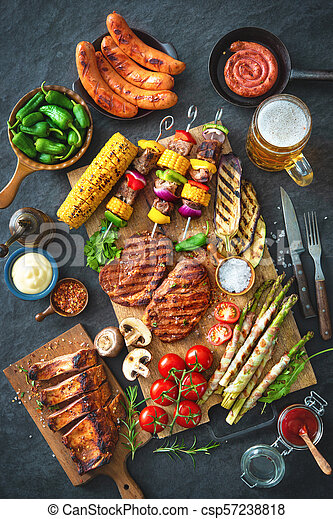 Grilled meat and vegetables on rustic stone plate - csp57238818