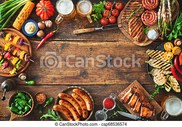 Grilled meat and vegetables on rustic wooden table - csp68536574