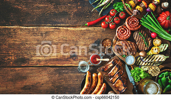 Grilled meat and vegetables on rustic wooden table - csp66042150