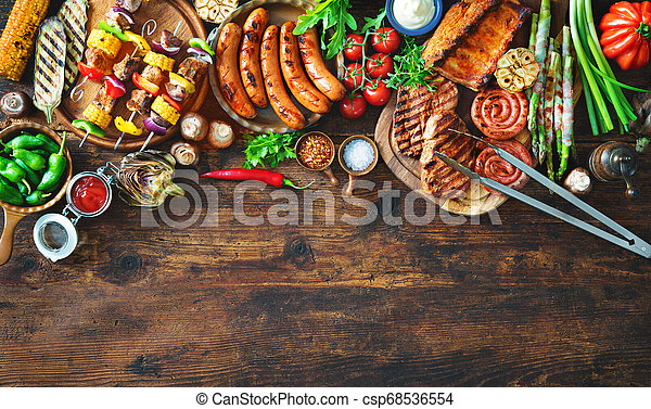 Grilled meat and vegetables on rustic wooden table - csp68536554