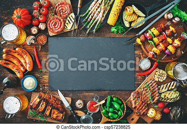 Grilled meat and vegetables on rustic wooden table - csp57238825