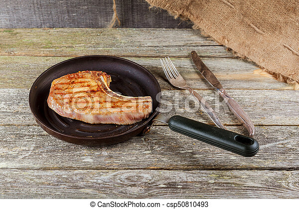 Grilled meat and vegetables on rustic wooden table. savory sauces and salt served with grilled steak on a rustic wooden - csp50810493