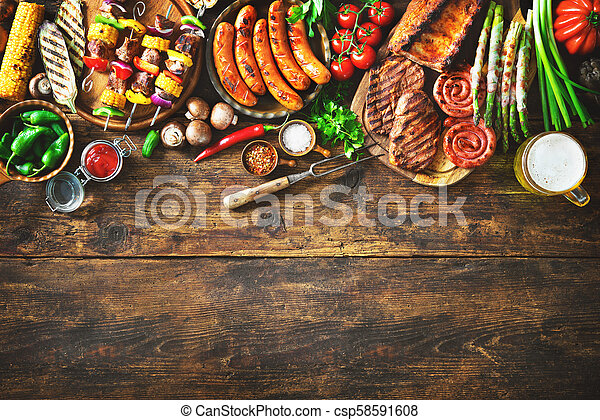 Grilled meat and vegetables on rustic wooden table - csp58591608