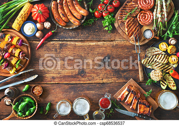 Grilled meat and vegetables on rustic wooden table - csp68536537