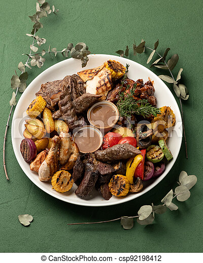 Grilled meat platter with vegetables isolated on green background. Barbecue concept. Vertical format, top view - csp92198412
