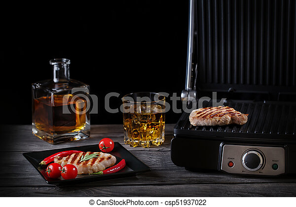 Grilled meat with vegetables and whiskey on wooden table - csp51937022