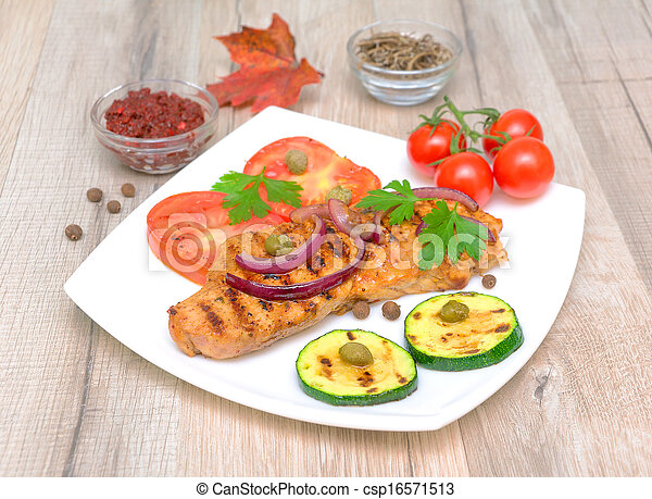 Grilled meat with vegetables on a wooden table - csp16571513