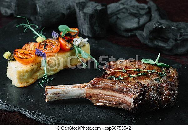 Grilled ribeye steak with polenta on dark background - csp50755542