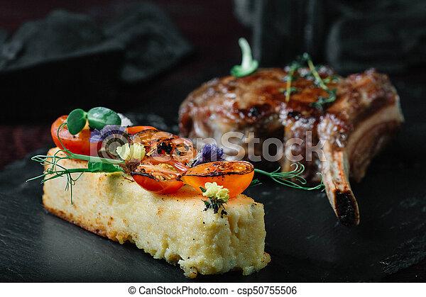 Grilled ribeye steak with polenta on dark background - csp50755506