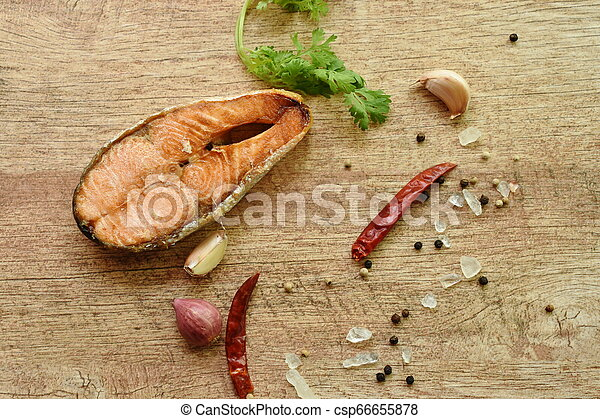 grilled salmon fish with salt and pepper on wooden background - csp66655878