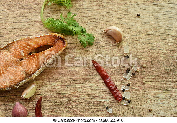 grilled salmon fish with salt and pepper on wooden background - csp66655916