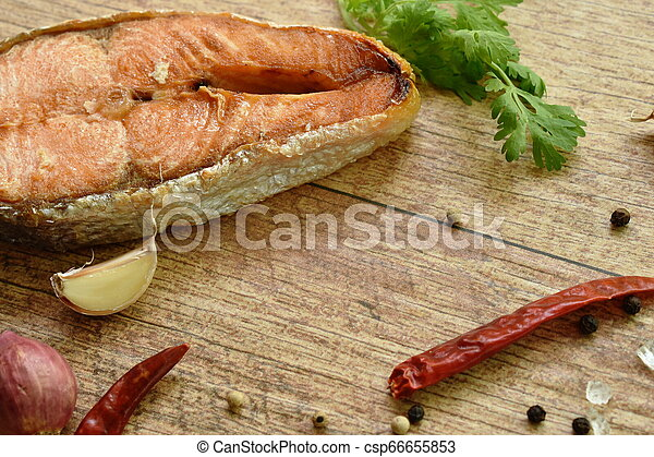 grilled salmon fish with salt and pepper on wooden background - csp66655853