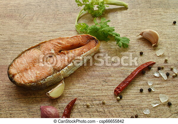 grilled salmon fish with salt and pepper on wooden background - csp66655842