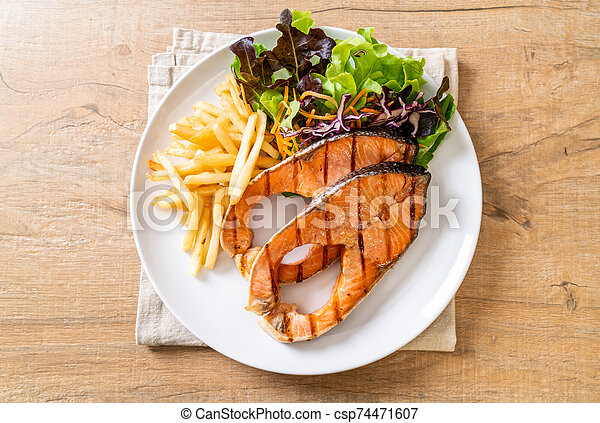 grilled salmon steak fillet with french fries - csp74471607