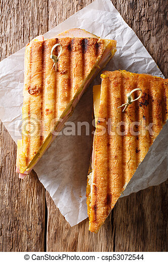 Grilled sandwich with ham, mustard, cheese, close-up on paper on the table. vertical view from above - csp53072544