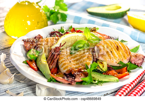 Grilled squids with vegetable on wooden background - csp48669849