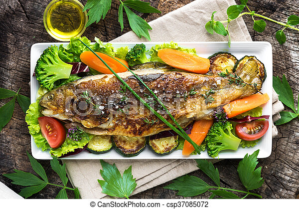 Grilled trout with vegetables on wooden background - csp37085072
