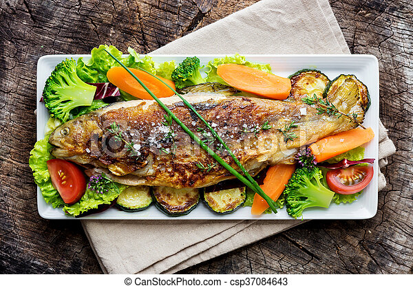 Grilled trout with vegetables on wooden background - csp37084643