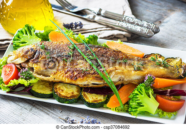Grilled trout with vegetables on wooden background - csp37084692