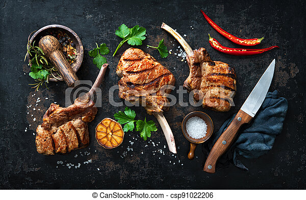 Grilled veal meat ribs cutlets with ingredients on rustic dark background - csp91022206