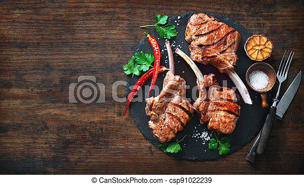 Grilled veal meat ribs cutlets with ingredients on wooden table - csp91022239