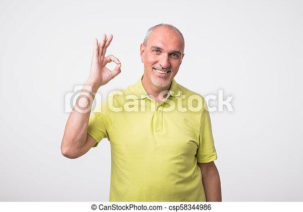 Un hombre guapo con camisa a cuadros aislado en antecedentes grises que muestra buena señal - csp58344986