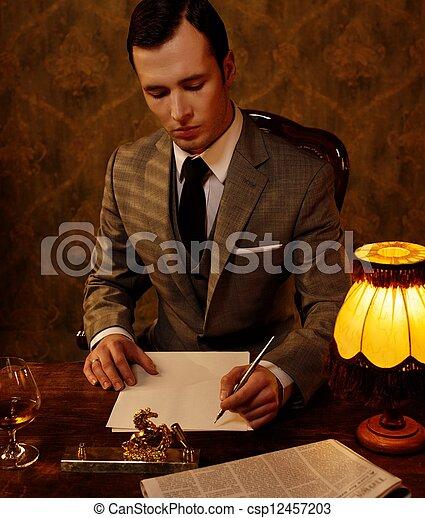 Retro hombre con traje gris sosteniendo un bolígrafo - csp12457203