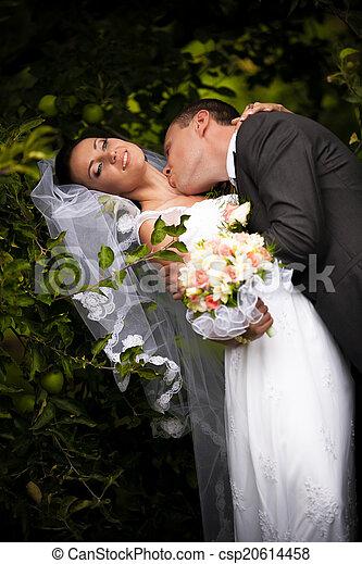 Groom kissing passionately bride in neck neck under tree - csp20614458