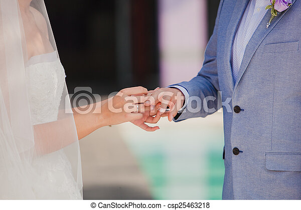 Groom wearing the diamond ring to bride hand in wedding stock