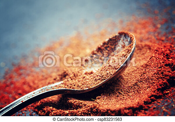 Ground sweet red paprika in a spoon on a dark background, selective focus, shallow depth of field - csp83231563