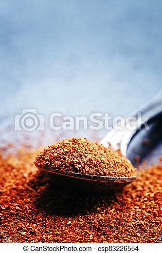 Ground sweet red paprika in a spoon on a dark background, selective focus, shallow depth of field - csp83226554