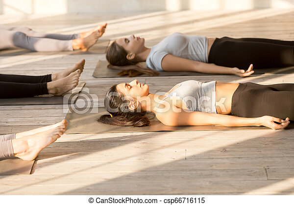 group of attractive women practicing yoga in corpse