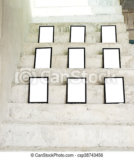 Group of black photo frames on rough concrete stair at building ...