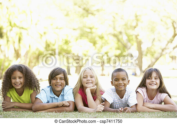 Group Of Children Lying On Stomachs In Park - csp7411750