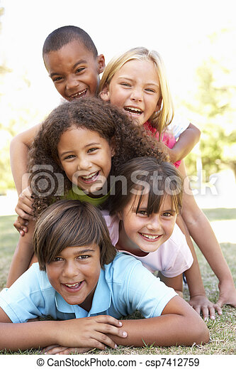 Group Of Children Piled Up In Park - csp7412759