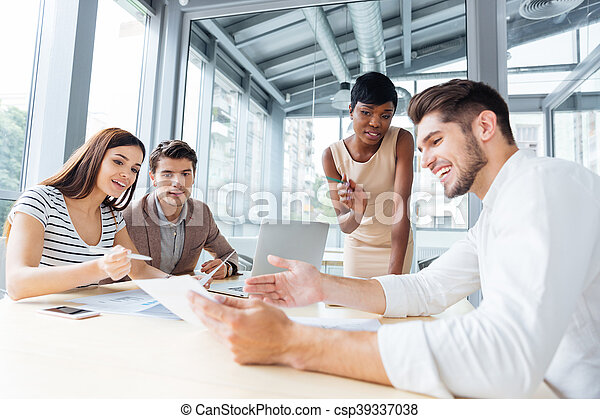 Group Of Colleagues Discussing Ideas And Planning Work In Office