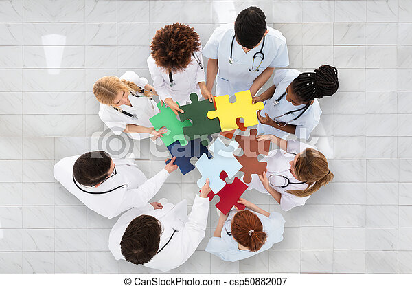 Group Of Doctors Holding Colorful Puzzle - csp50882007