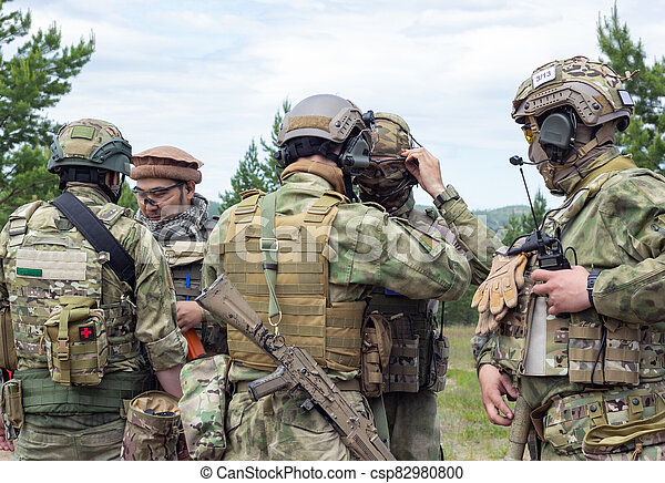 Group of fully armed american soldiers getting ready for the fight on military range, active military game airsoft. - csp82980800